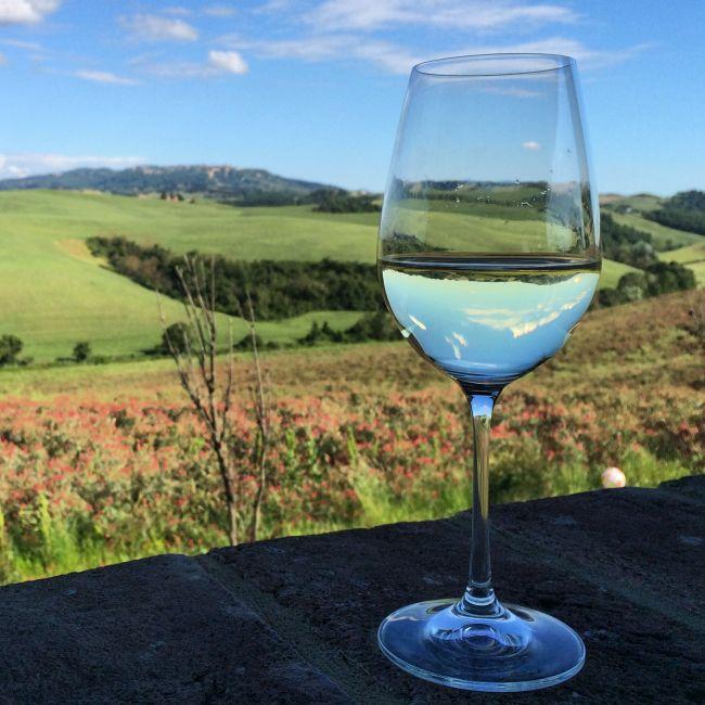 Wein vor Toskana-Landschaft